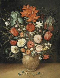 Roses, tulips, carnations and other flowers in a vase on a stone ledge