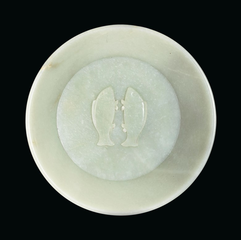 An important and extremely rare imperially inscribed greenish-white jade 'twin fish' washer, China, Qing dynasty, Qianlong incised four-character mark and of the period, dated by inscription to the cyclical bingwu year, corresponding to 1786. 10  in (25.4  cm)  diameter, hongmu stand. Sold for $2,895,000 on 20 March 2019 at Christie's in New York