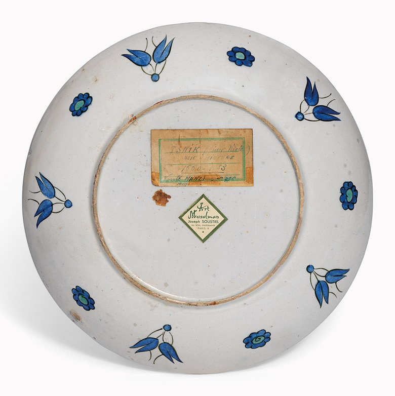 The reverse of a fine rimless Iznik pottery dish, showing old connection labels. Ottoman Turkey, c. 1575. 11¾ in (29.8 cm) diameter. Sold for £86,500 on 21 April 2016