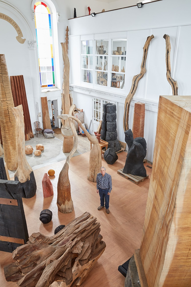 The artist pictured with some of his wooden sculptures. Photograph by Robin Friend