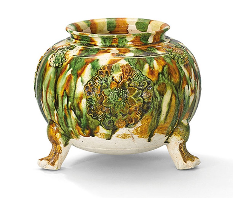 A sancai-glazed applique-decorated tripod jar. Tang dynasty (618-907). 5¼  in (13.3 cm) high, box. This  work was offered in The Pavilion Sale on 4 October 2016 at Christie's Hong Kong and sold for HK$275,000$US35,600