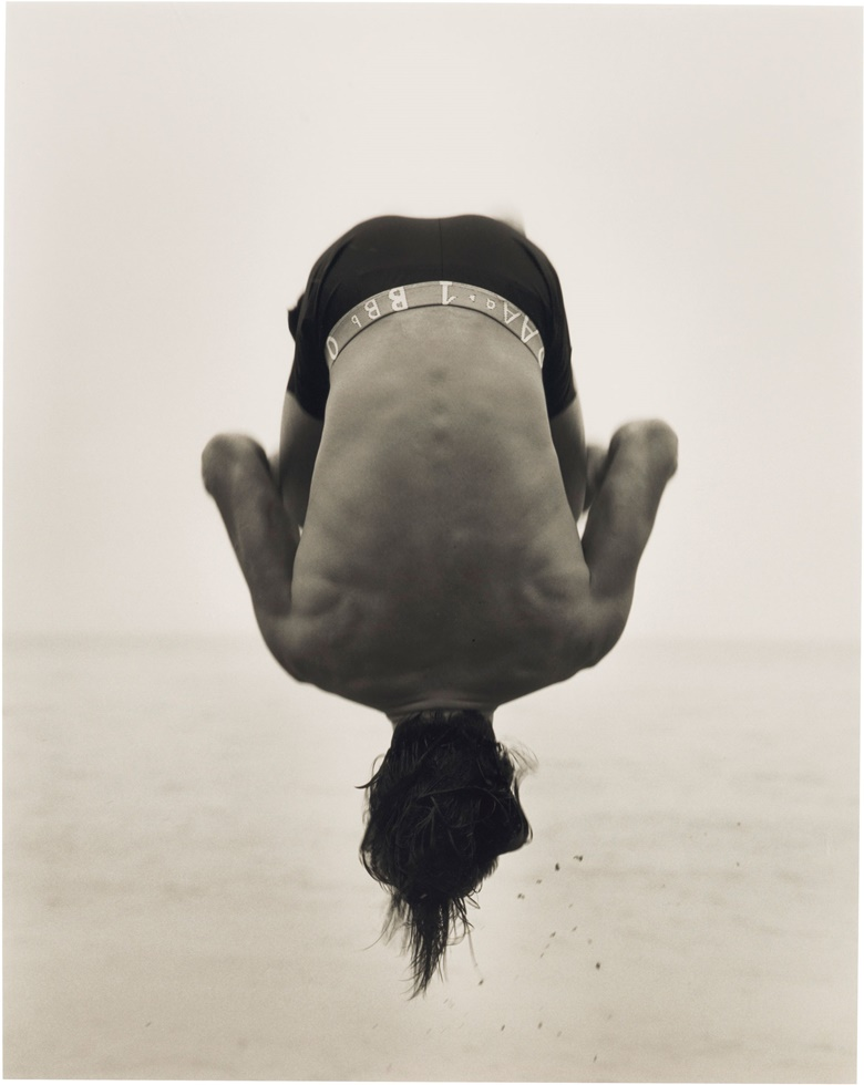 Herb Ritts (1952–2002), Backflip, Paradise Cove, 1987. Gelatin silver print signed, titled, dated and numbered '125' in pencil (mount, verso). Image 19 x 15¼ in (48.3 x 38.7 cm), sheet 20 x 16 in (50.8 x 40.7 cm), mount 21½ x 17½ in (54.6 x 44.5 cm). This print is number 1 from the edition of 25 plus 3 artist's proofs. This lot is offered in Photographs