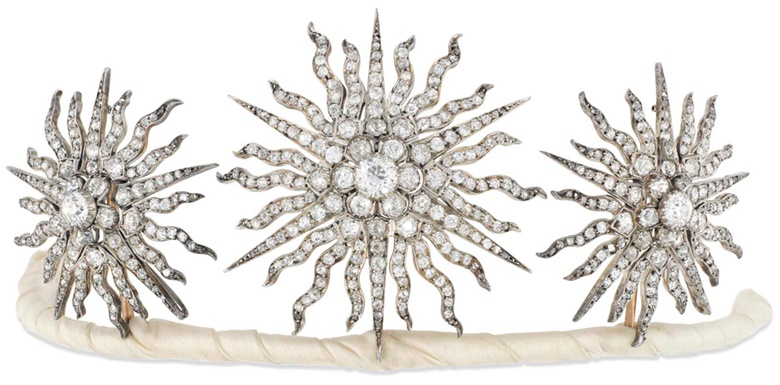 An Edwardian diamond tiara. Designed as a group of three old brilliant-cut diamond graduated sunburst star panels, each with central diamond cluster to a radiating surround of similarly set rays, mounted in silver and gold, detaching to form three brooches or a hair slide, four additional fittings, circa 1900. Largest star 5.7 cm, in fitted case. Sold for £15,000 on 30 November 2016  at