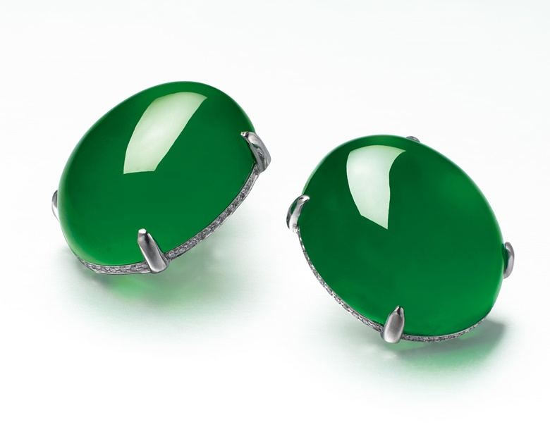 A magnificent pair of jadeite and diamond ear studs. Each set with a thick high-domed jadeite cabochon of very even brilliant emerald green colour and high translucency, to the brilliant-cut diamond gallery, the back enhanced by diamond-set scrolls, mounted in 18k white gold, cabochons approximately 26.41 x 21.81 x 11.08 and 26.40 x 21.92 x 11.61 mm. Sold for HK$51,640,000 on 25 November 2014