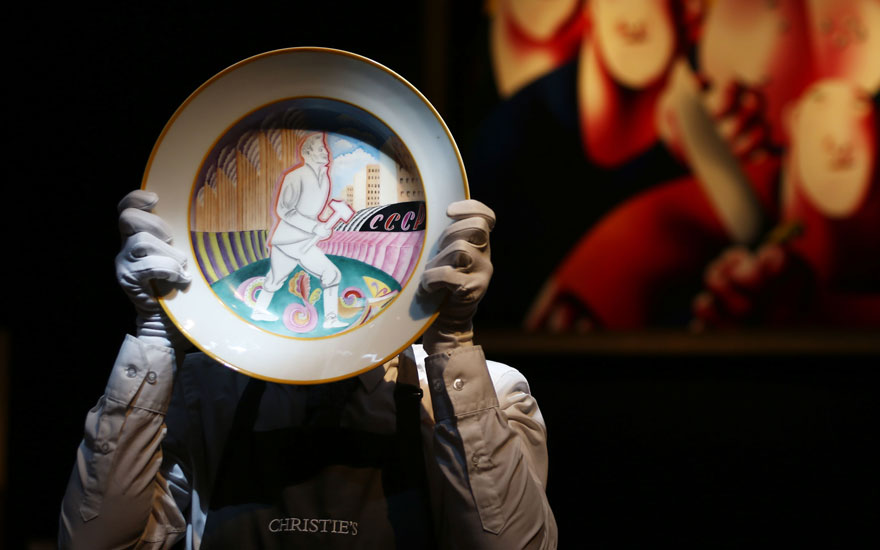 A Christie's technician holds a Soviet porcelain propaganda platter made by the Imperial Porcelain Factory and the State Porcelain Factory, Petrograd, 1923, which sold for £106,250 in the