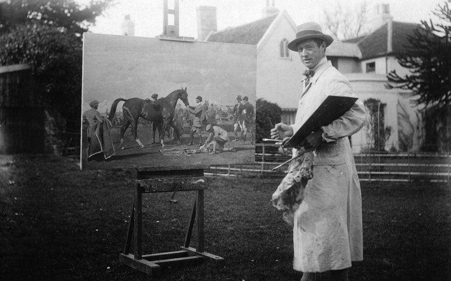 Sir Alfred Munnings photographed at work on a racing scene in 1925. Photo Claude HarrisGetty Images. Artwork © Estate of Sir Alfred Munnings, Dedham, Essex. All rights reserved, DACS 2018