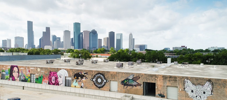 The Houston skyline as viewed from Sawyer Yards — warehouses that now serve as artistic spaces