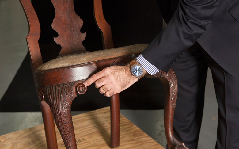 John Hays points out the deeply-carved S-scrolls — or volute — at both knees of the chair