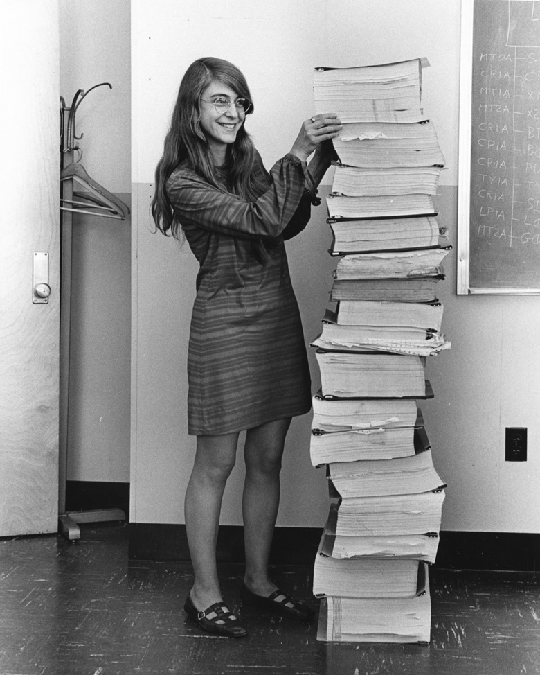 Margaret Hamilton photographed in 1969, standing next to a stack of code print-outs for Apollo in-flight software. Courtesy MIT Museum
