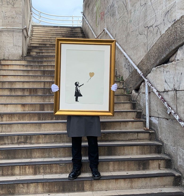 Banksy (b. 1975), Girl with Balloon - Colour AP (Gold), 2004. Screenprint in black and gold, signed. Image 390 x 260 mm, sheet 695 x 495 mm. Sold for £395,250 in Banksy I cant believe you Morons actually buy this sht, 11-24 September, Online. Artwork Courtesy of Pest Control Office