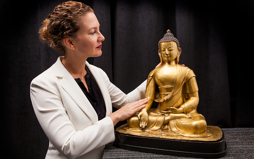 Jacqueline Dennis Subhash with a rare gilt-bronze figure of Buddha Ratnasambhava, Nepal, 17th-18th century. Height 46 cm (18⅛ in). Estimate $400,000-600,000. Offered in Indian, Himalayan &