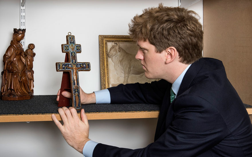 Christie's Early European Sculpture specialist Milo Dickson with a Limoges 'Patriarchal' cross. Offered in Old Masters Evening Sale on 3 December 2019 at Christie's in