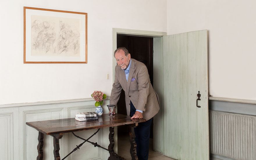 Michael Peppiatt at home in France with his Spanish travelling table, c. late-17th  early-18th century. Photograph by Fred Lahache. Artwork Dado (Miodrag Djuric),  Portrait of Michael Peppiatt, 1979.