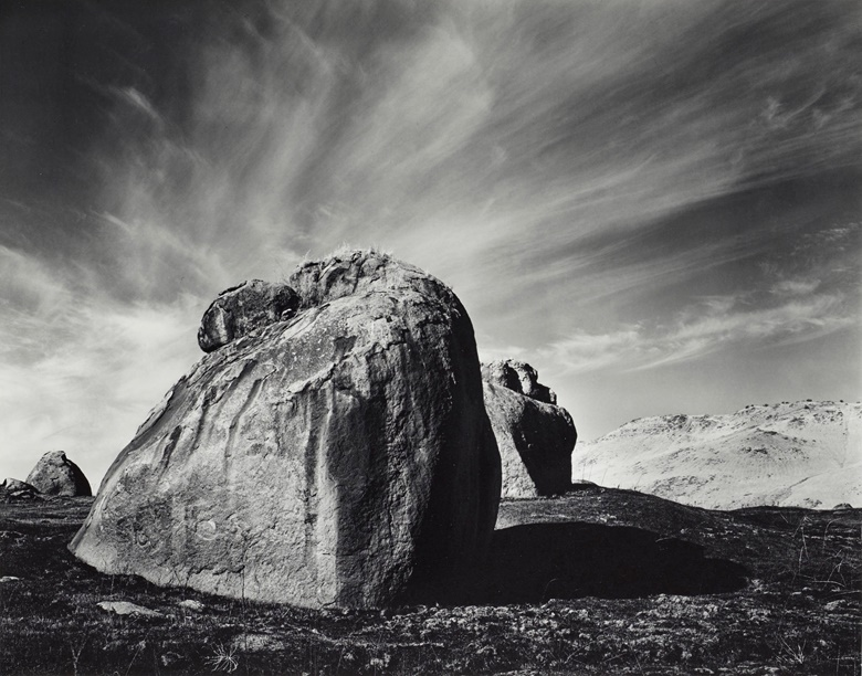 Ansel Adams (1902–1984), Rocks and Clouds, Sierra Nevada Foothills, California, 1938. Gelatin silver print, mounted on board, printed 1979, signed in pencil (mount, recto); titled and dated in ink in photographers Carmel credit stamp (mount, verso). Mount 15⅞ x 19⅞ in (40.3 x 50.5 cm). Estimate $8,000-$12,000. Offered in Ansel Adams and the American West Photographs from the Center for