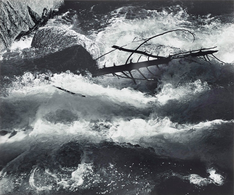 Ansel Adams (1902–1984), Rushing Water, Merced River, Yosemite National Park, California, c. 1955. Gelatin silver print, mounted on board signed in ink (mount, recto). Mount 13⅞ x 17⅞ in (35.4 x 45.4 cm). Estimate $4,000-6,000. Offered in Ansel Adams and the American West Photographs from the Center for Creative Photography, 27 May–4 June 2020, Online. Artwork © The Ansel Adams