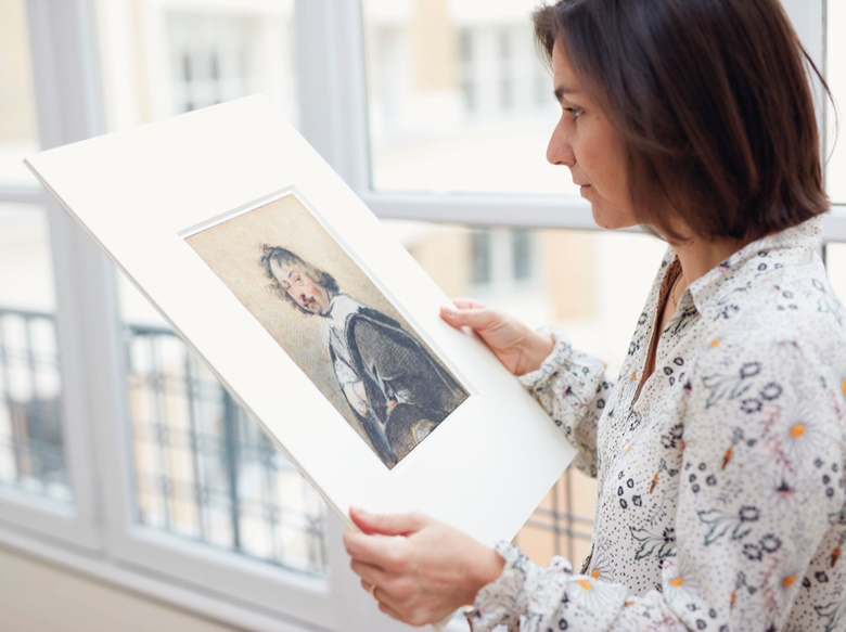Specialist Hélène Rihal with a portrait of an anonymous man wearing a large black coat over a wide-collared white shirt — perhaps evidence for a lesson in the French tradition of drawing 'trois crayon'